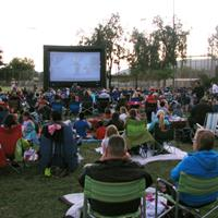 People sit together on open grass area watching movie on large projector screen